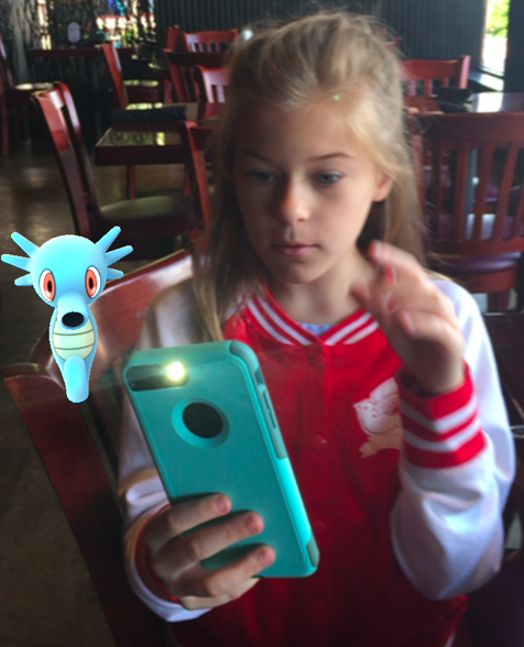 Young Gen Z girl with iPhone playing Pokemon Go